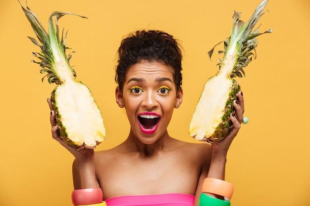 Retrato de mulher de raça mista encantado com aparência de moda segurando duas metades de abacaxi em ambas as mãos isoladas, sobre parede amarela