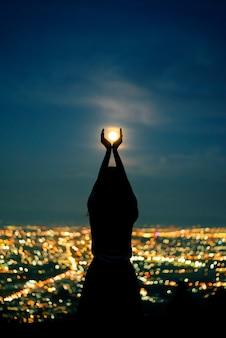 Retrato de mulher de silhueta com lua cheia na cidade à noite luz bokeh de fundo