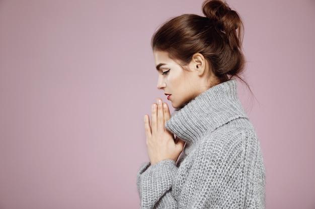Retrato de mulher de suéter cinza rezando em perfil na rosa