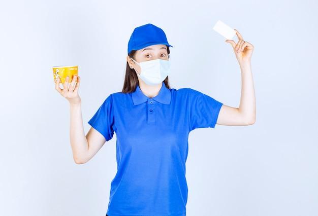 Retrato de mulher de uniforme e máscara médica segurando um cartão