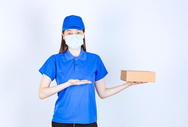 Retrato de mulher de uniforme e máscara médica segurando uma caixa de papel