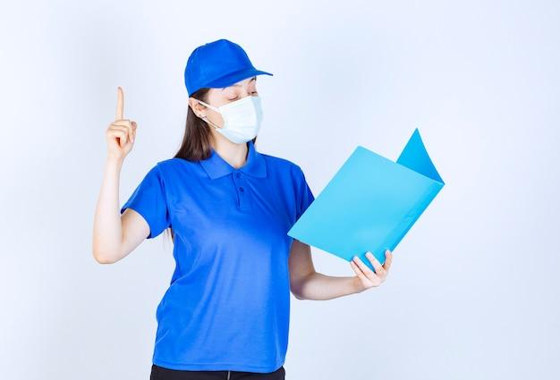 Retrato de mulher de uniforme e máscara médica segurando uma pasta