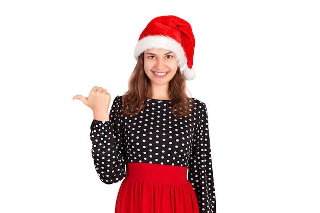 Retrato de mulher de vestido, apontando à esquerda com o polegar e sorrindo. garota emocional no chapéu de natal papai noel isolado