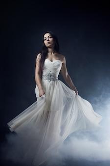 Retrato de mulher de vestido branco longo, estilo místico, misterioso, no escuro