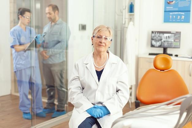 Retrato de mulher dentista sênior esperando paciente doente no consultório do hospital de estomatologia durante exame médico