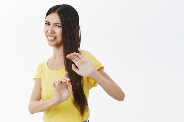 Retrato de mulher descontente, arrogante e temperamental levantando as mãos para se proteger de algo nojento