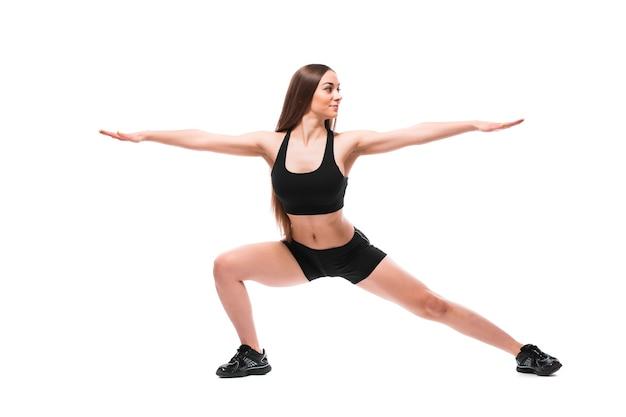 Retrato de mulher desportiva em roupas esportivas, malhando, fazendo exercícios isolados no fundo branco