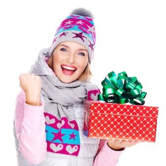 Retrato de mulher divertida com um presente em um casaco de inverno isolado no branco