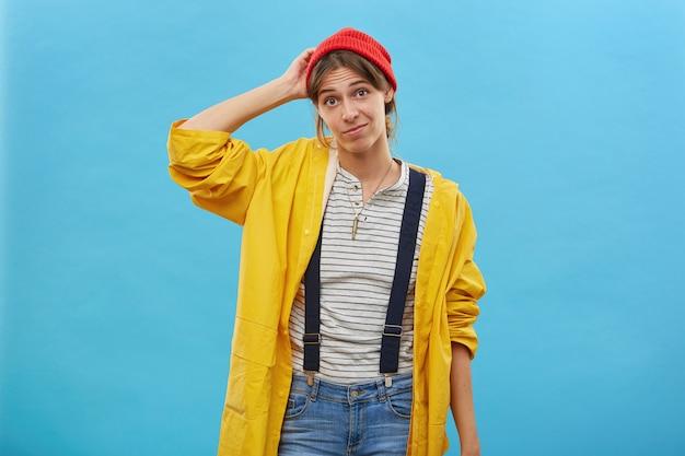 Retrato de mulher duvidosa vestida casualmente, coçando a cabeça com a mão, sem saber o que fazer isolado sobre a parede azul. mulher bonita em um anoraque amarelo solto, incerta, tendo dúvidas