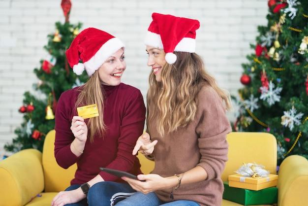 Retrato de mulher e amigo, mostrando um cartão de crédito em branco nas férias de natal, compras de natal e ano novo na internet, pagamento com cartão de crédito.