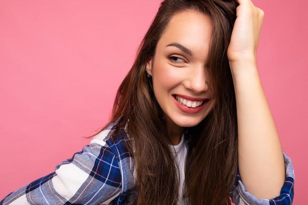 Retrato de mulher elegante alegre positiva em roupa hipster isolado no fundo rosa com espaço de cópia.
