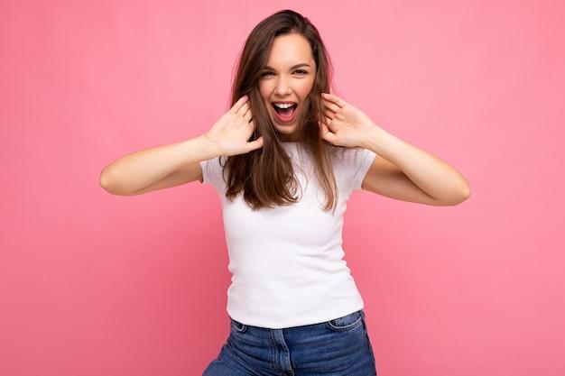 Retrato de mulher elegante alegre positiva em t-shirt casual para mock up isolado no fundo rosa com espaço de cópia.
