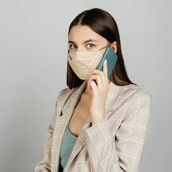 Retrato de mulher elegante com máscara usando celular