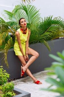 Retrato de mulher elegante com vestido amarelo e lenço no pescoço no jardim tropical