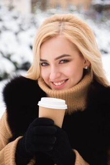 Retrato de mulher elegante de estilo europeu tomando café em winter park