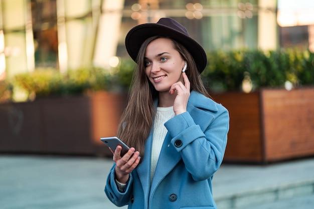 Retrato de mulher elegante hipster morena na moda no chapéu e com um casaco azul com fones de ouvido brancos sem fio, gosta e ouve música no centro da cidade. pessoas e tecnologia modernas