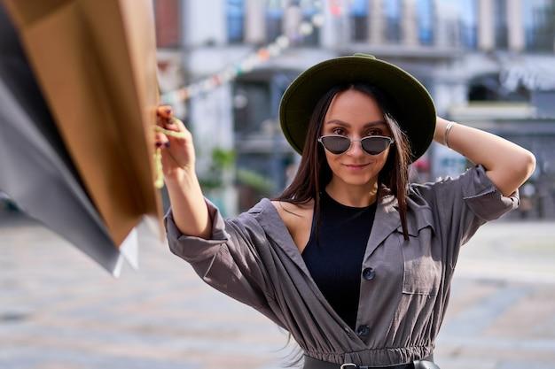 Retrato de mulher elegante, jovem e sorridente hippie viciada em compras com sacolas de papel