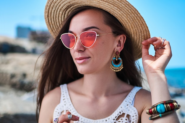 Retrato de mulher elegante lindo verão brilhante usando um chapéu de palha, brincos grandes e óculos de sol vermelhos no mar