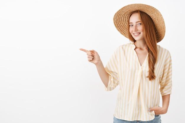 Retrato de mulher elegante ruiva feliz e feminina encantadora aproveitando o dia de verão na praia com chapéu de palha e blusa amarela da moda apontando para a esquerda