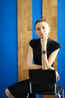 Retrato de mulher elegante, sentado na cadeira e posando na câmera. mulher jovem e bonita com cabelo curto. senhora na moda e elegante de vestido preto. conceito de modelagem