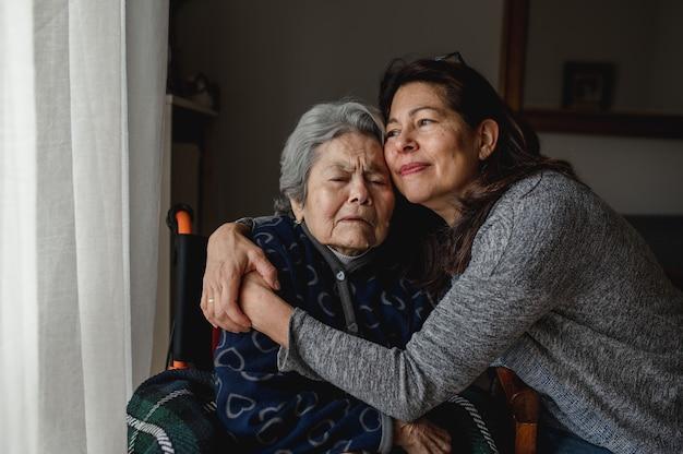 Retrato de mulher em cadeira de rodas, abraçando a filha com cara positiva. terceira idade, conceito de atendimento domiciliar.