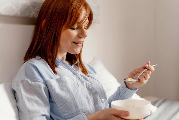 Retrato de mulher em casa comendo
