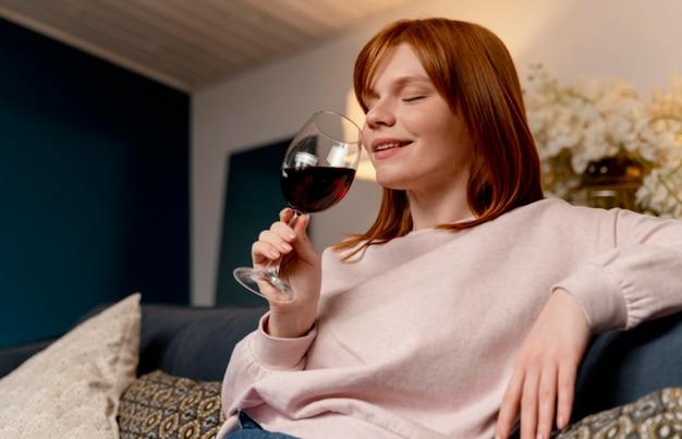 Retrato de mulher em casa relaxando com uma taça de vinho