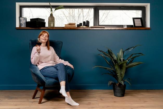 Retrato de mulher em casa relaxando na cadeira