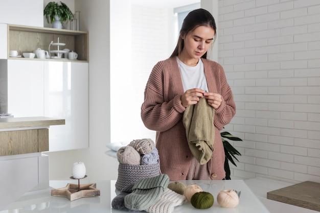 Retrato de mulher em casa tricotando