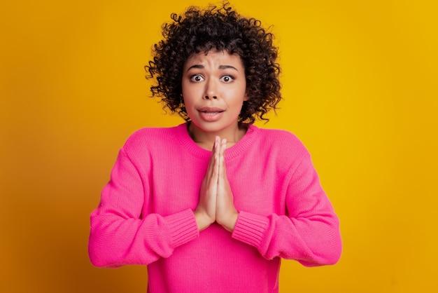 Retrato de mulher em close-up, rosto preocupado, implorar gesto isolado fundo de parede amarela