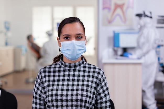 Retrato de mulher em consultório odontológico, olhando para a câmera usando máscara facial, sentado na cadeira na clínica de sala de espera enquanto o médico trabalha