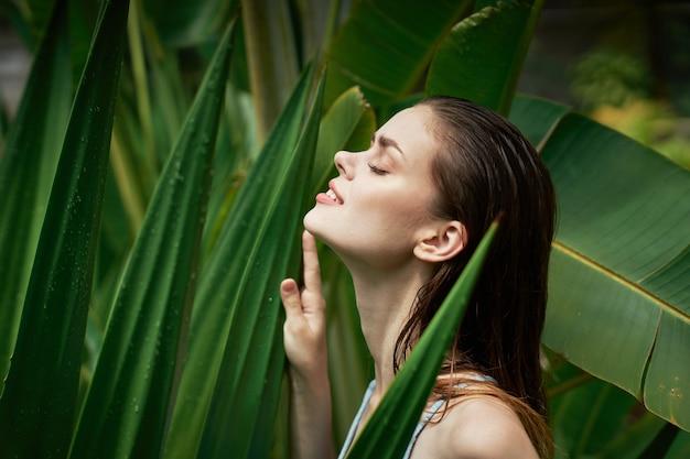 Retrato de mulher em copos em um espaço de folhas verdes de palmeiras, rosto bonito