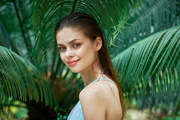 Retrato de mulher em copos em um fundo de folhas verdes de palmeiras, rosto bonito