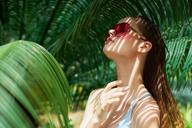 Retrato de mulher em copos em um verde folhas de palmeiras, rosto bonito