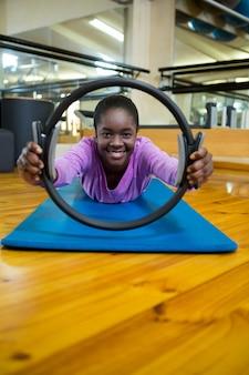 Retrato de mulher em forma se exercitando com anel de pilates no estúdio de fitness