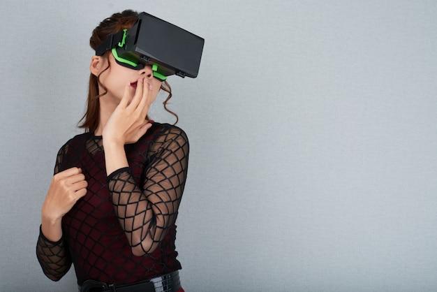 Retrato de mulher em óculos de realidade virtual, tocando seus lábios em pé contra cinza