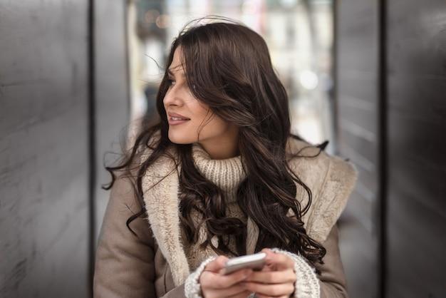 Retrato de mulher em pé na passagem e desviar o olhar. no telefone inteligente de mãos.