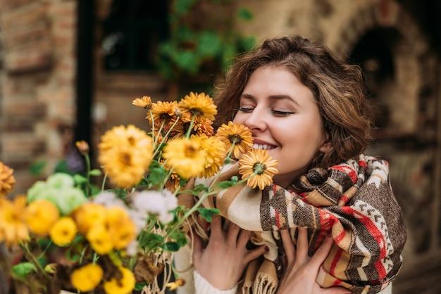 Retrato de mulher em pé perto de flores amarelas e cheirando.