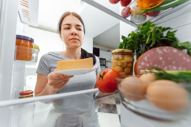 Retrato de mulher em pé perto de geladeira aberta cheia de alimentos saudáveis. retrato de mulher