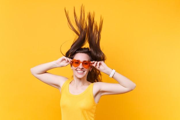 Retrato de mulher em quadrinhos engraçado animado riso alegre em óculos laranja com esvoaçantes cópia espaço de cabelo isolado em fundo amarelo. emoções sinceras de pessoas, conceito de estilo de vida. área de publicidade.
