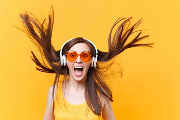 Retrato de mulher em quadrinhos engraçado animado riso alegre em óculos laranja em fones de ouvido com esvoaçantes cabelos isolados no fundo amarelo. emoções sinceras de pessoas, conceito de estilo de vida. área de publicidade