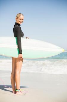 Retrato de mulher em roupa de neoprene segurando uma prancha de surf na praia