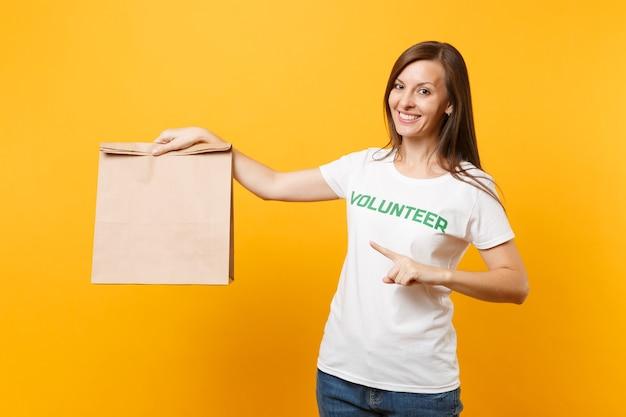 Retrato de mulher em t-shirt branca escrito inscrição verde título voluntário segurar o saco de papel ofício em branco para take-away isolado no fundo amarelo. assistência voluntária gratuita para ajudar conceito de graça de caridade