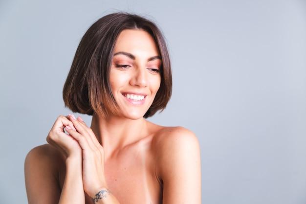 Retrato de mulher em topless com maquiagem e pele bronzeada suave e macia na parede cinza