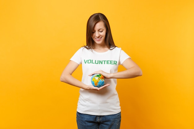 Retrato de mulher em uma camiseta branca com voluntário de título verde de inscrição escrita segurar nas palmas das mãos globo do mundo terra isolado em fundo amarelo. ajuda de assistência gratuita voluntária, conceito de graça de caridade.