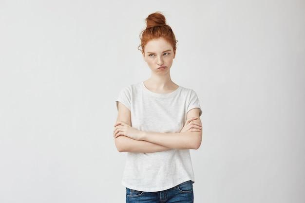 Retrato de mulher emotiva ruiva descontente com braços cruzados.
