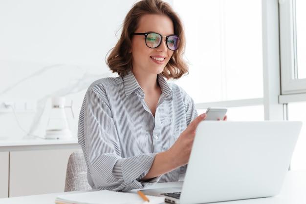Retrato de mulher encantadora de óculos e camisa listrada, usando telefone celular enquanto localização no local de trabalho no quarto branco