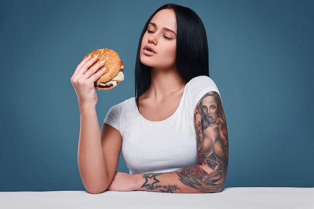 Retrato de mulher encantadora tatuagem segurando o hambúrguer