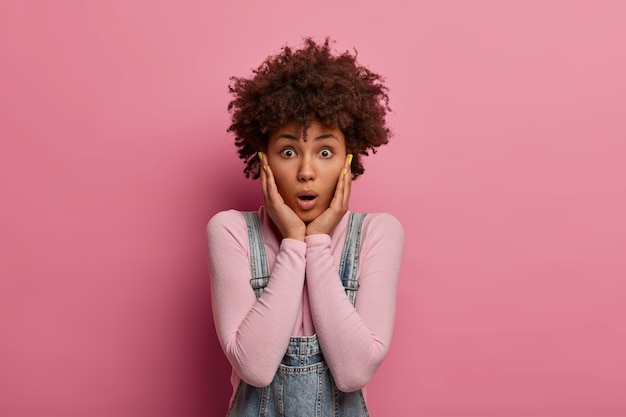 Retrato de mulher encaracolada atônita agarra o rosto e o encara com olhos arregalados, fofoca sobre algo incrível, vestida casualmente, posa contra a parede rosa, ansiosa com o terrível acidente.