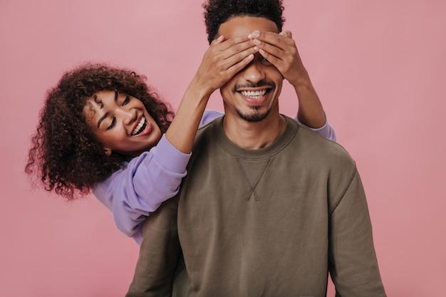 Retrato de mulher encaracolada fechando os olhos do namorado para surpreendê-lo